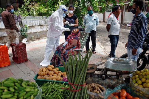Sanitario realiza una prueba de coronavirus a una vendedora de alimentos en Ahmedabad, India