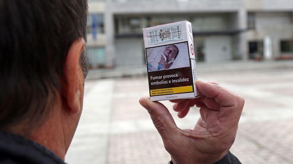 El denunciante, ayer en Boiro, mostrando una cajetilla en la que se reconoce intubado.