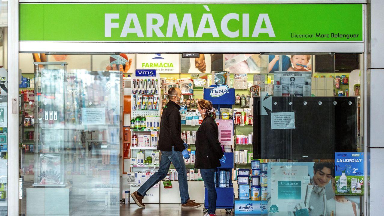 Varias personas se acercan a una farmacia en Barcelona, este sábado. El Diario Oficial de la Generalitat (DOGC) publica la resolución del Govern que decreta el cierre de bares, cafeterías, restaurantes y discotecas, entre otros establecimientos, como medida de prevención del coronavirus