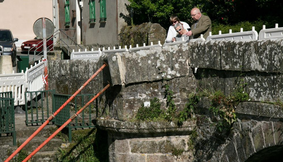 Villa Magdalena.Varios vecinos observan la zona dañada del puente medieval.