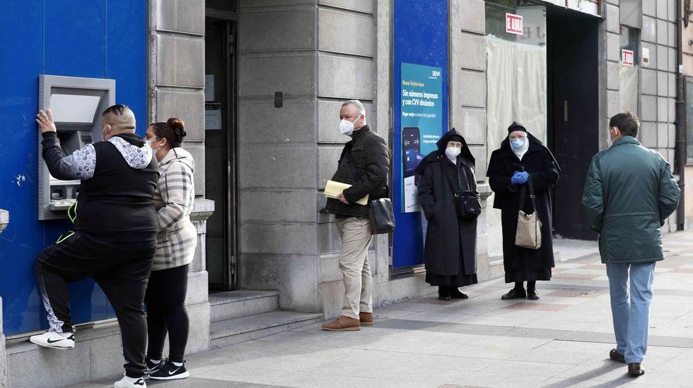 Varias personas esperando ante una entidad bancaria en Oviedo