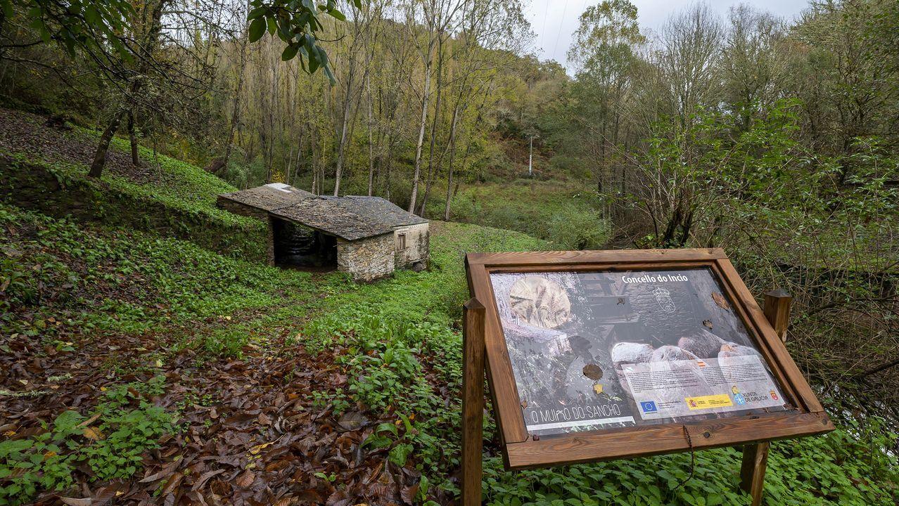 Un panel informativo de la ruta frente a un antiguo molino que forma parte del itinerario