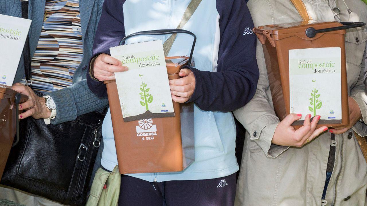 Cubo marrón dedicado a los residuos orgánicos.Una voluntaria participa en uno d elos programas de COGERSA para limpiar un monte en Asturias