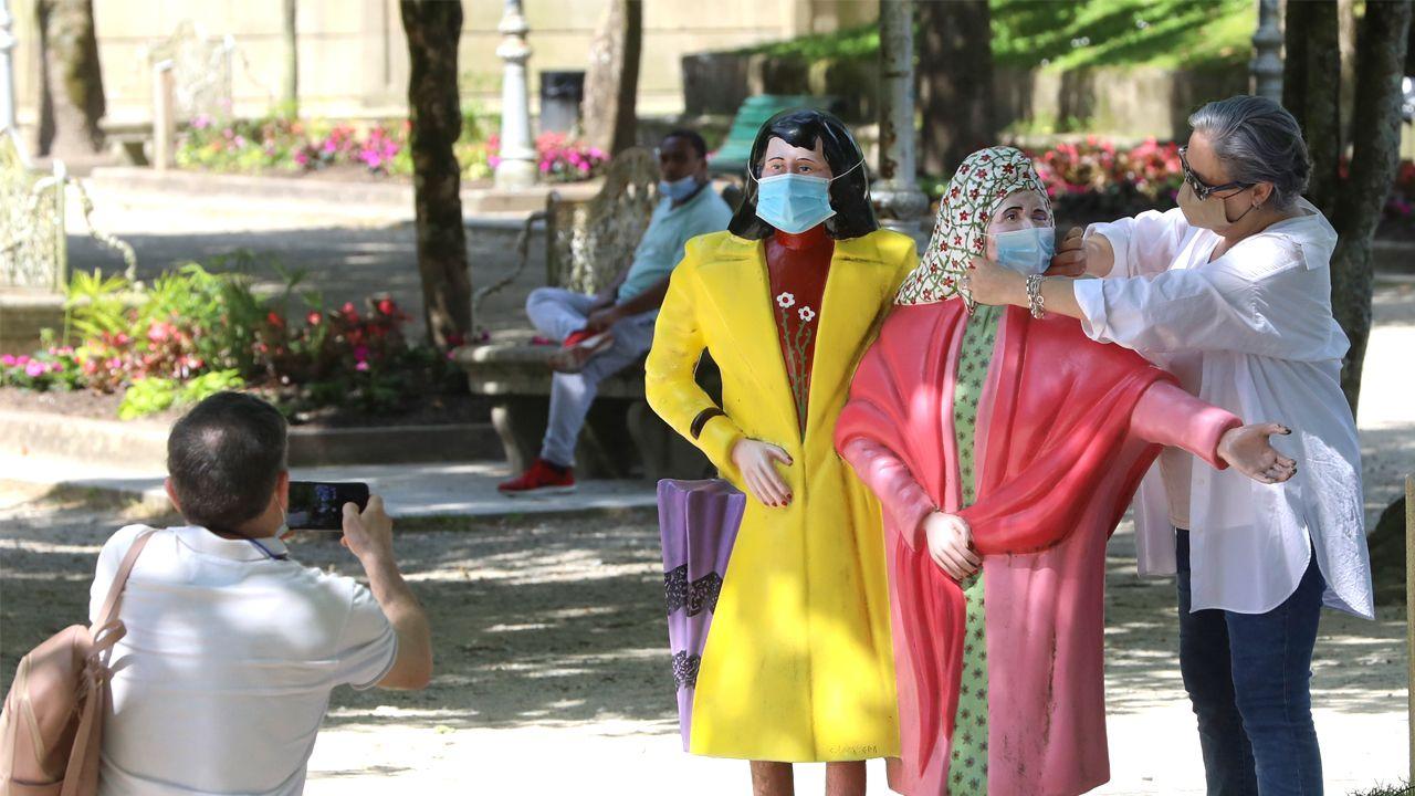 Una mujer pone mascarillas a las Marías, en la Alameda de Santiago