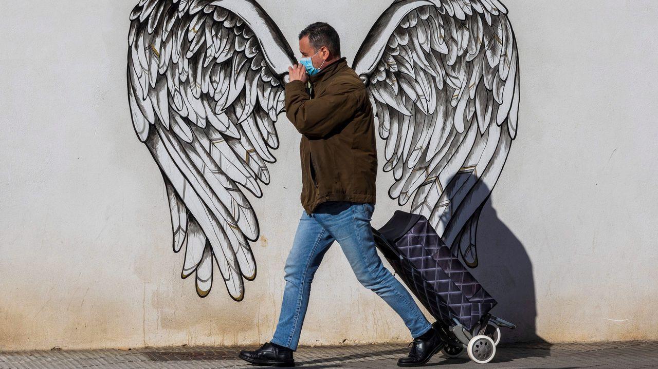 Un hombre pasa ante un mural en Siero