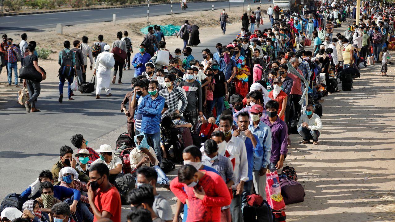Trabajadores migrantes y sus familias hacen cola en la estación de Uttar Pradesh, en La India, para intentar regresar a sus hogares
