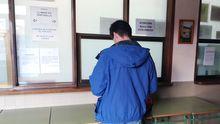 Un alumno con mascarilla esperan a ser antendido en la secretaría del instituto Jovellanos, de Gijón