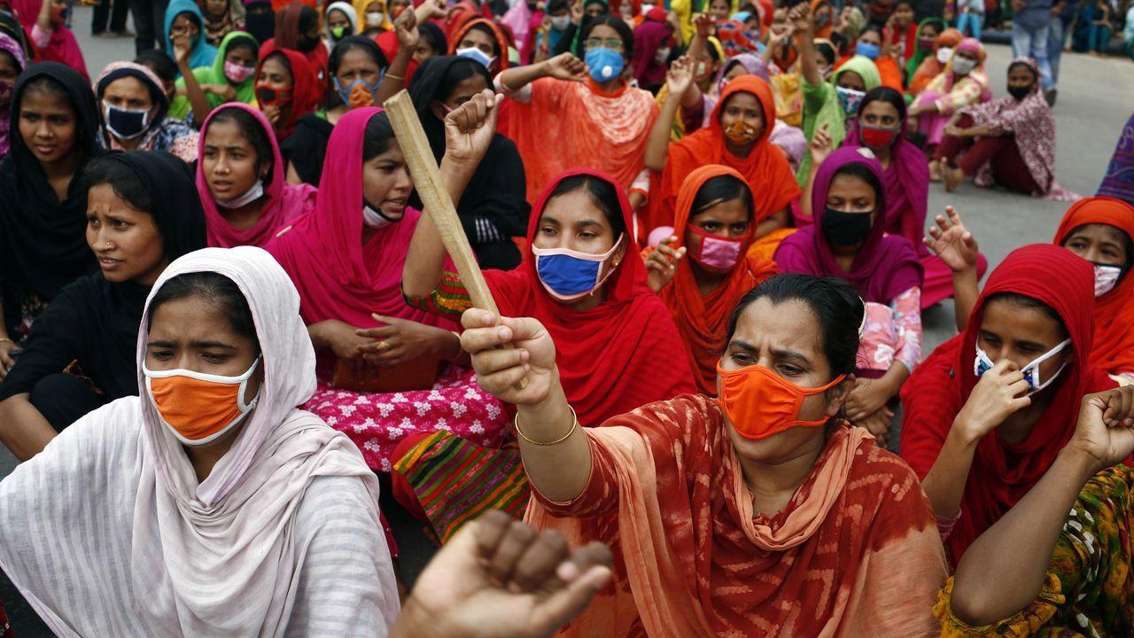 Trabajadoras de la confección de Bangladesh, algunas con máscaras protectoras, gritan consignas y bloquean una carretera durante una protesta para exigir el pago de salarios en Dhaka. Miles de trabajadoras del sector no fueron pagadas por las fábricas después de que se cancelaran exportaciones por valor de alrededor de tres mil millones de dólares debido a la pandemia causada por el coronavirus