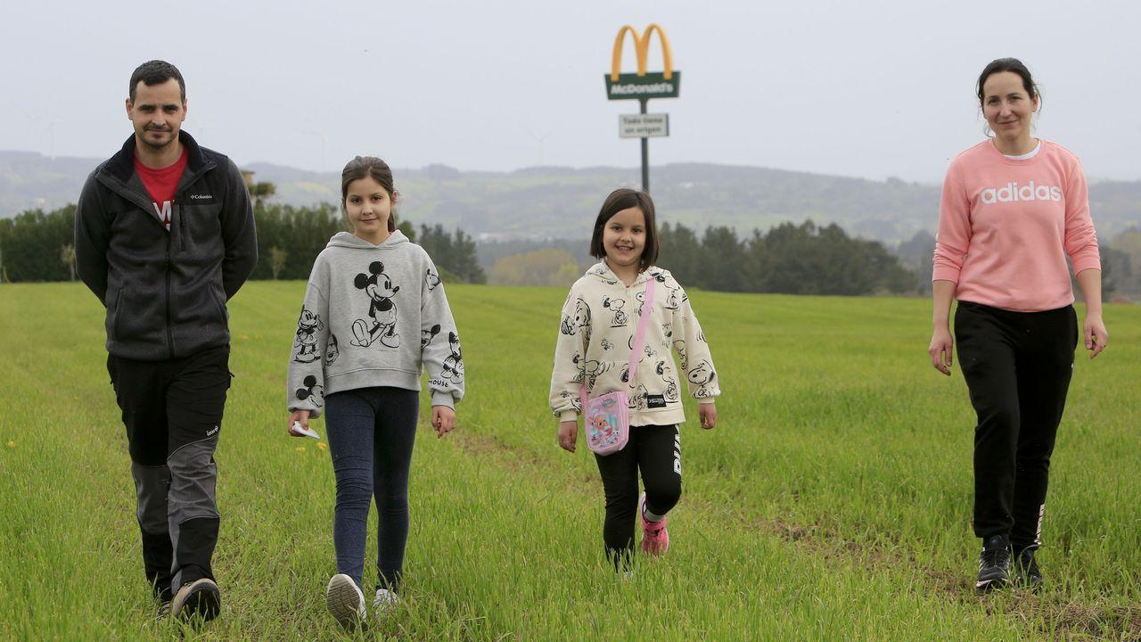 José García y Zeltia González, paseando con sus hijas por una de las fincas cercanas a la explotación, con el poste promocional detrás