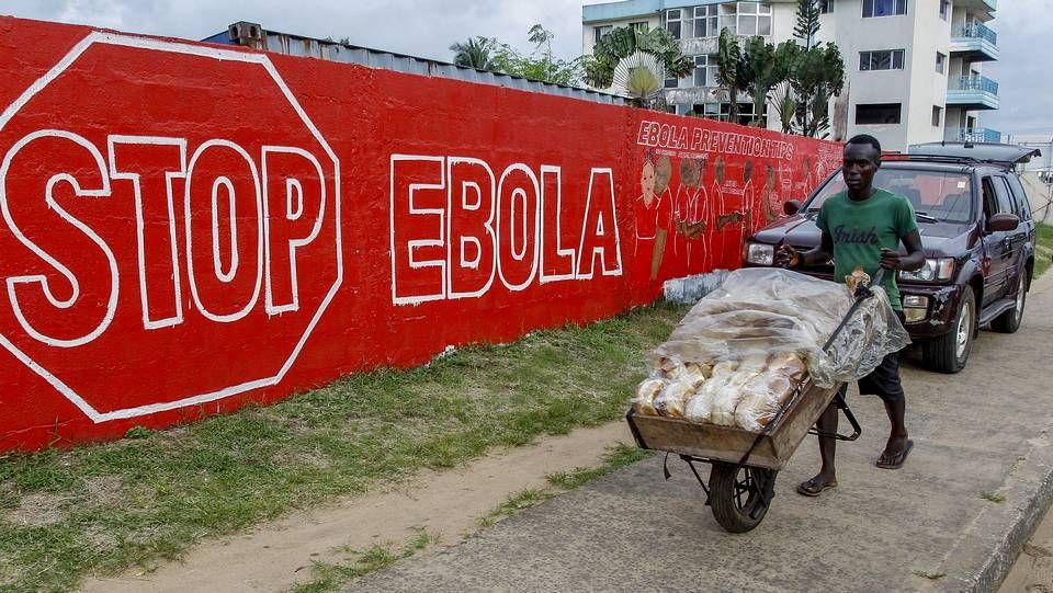 Un hombre lleva pan junto a un muro en con un anuncio de la campaña creada para combatir el brote de ébola en África Occidental, en Monrovia, Liberia