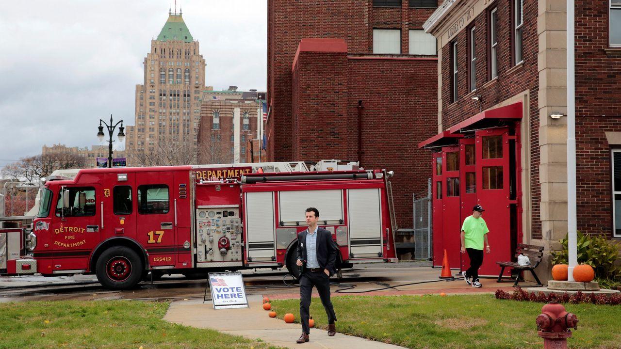 Un hombre sale de un parque de bomberos, empleado como colegio electoral
