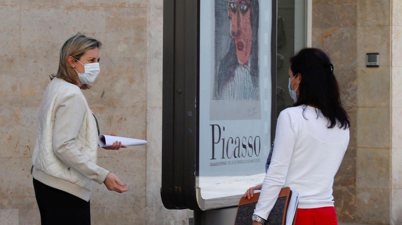 Dos mujeres con mascarilla conversan en una calle de Oviedo.