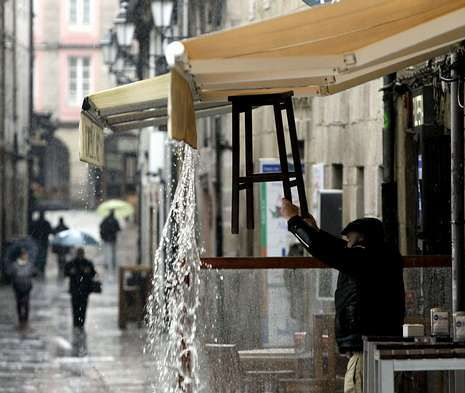 Un hostelero retira el agua de lluvia de su toldo en Lugo, donde ya ha llovido 20 días en marzo.