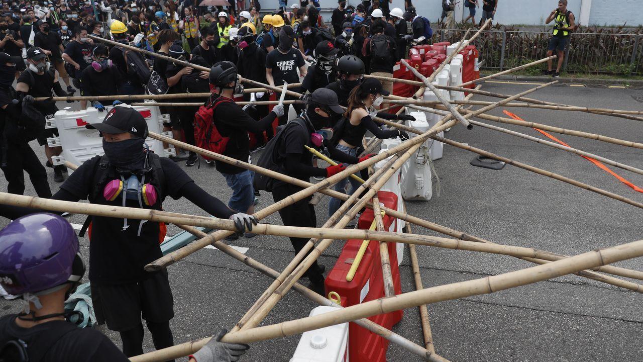 Los manifestantes se defienden en kwun Tong con palos y montan barricadas para evitar a los agentes antidisturbios