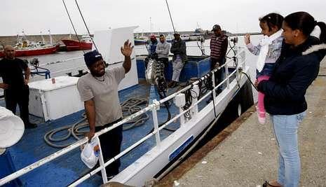 Tripulantes del «Pixuetinas», ayer en Burela, antes de zarpar, despidiéndose de sus parientes.