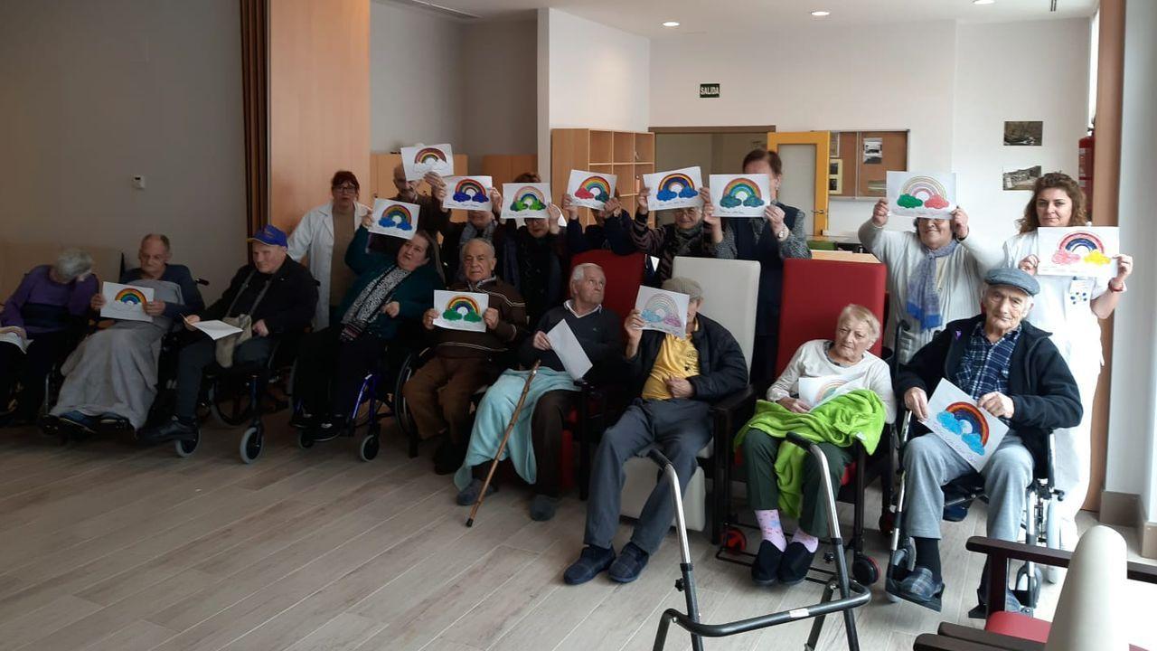 Usuarios y trabajadores del centro de mayores de A Fonsagrada con carteles de ánimo por el coronavirus