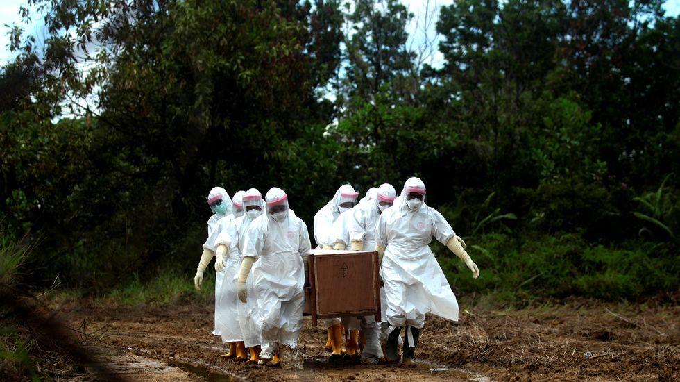 Funcionarios municipales portan un ataúd en un enterramiento masivo en Tarakan, Indonesia