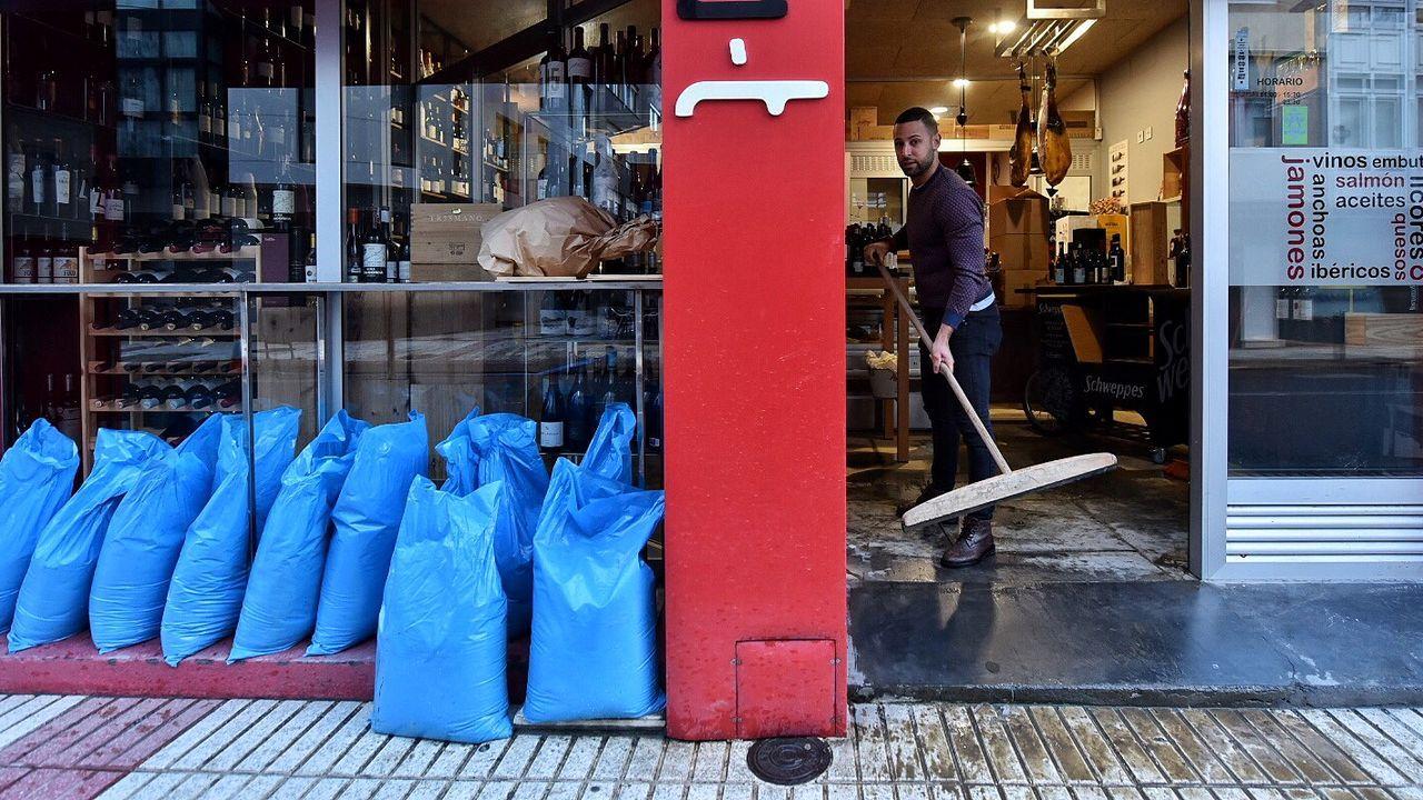 Imagen de un hostelero limpiando su negocio en una de las inundaciones que ha sufrido la zona de As Brañas