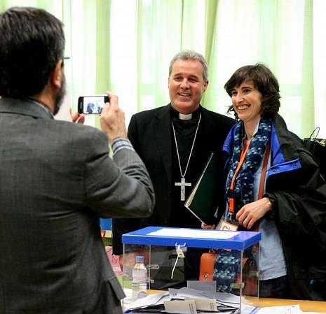<span lang= es-es >El obispo de Bilbao, al frente de una mesa</span>. Una mujer que se acercó a votar pidió que le sacaran una foto con el obispo de la capital vizcaina.