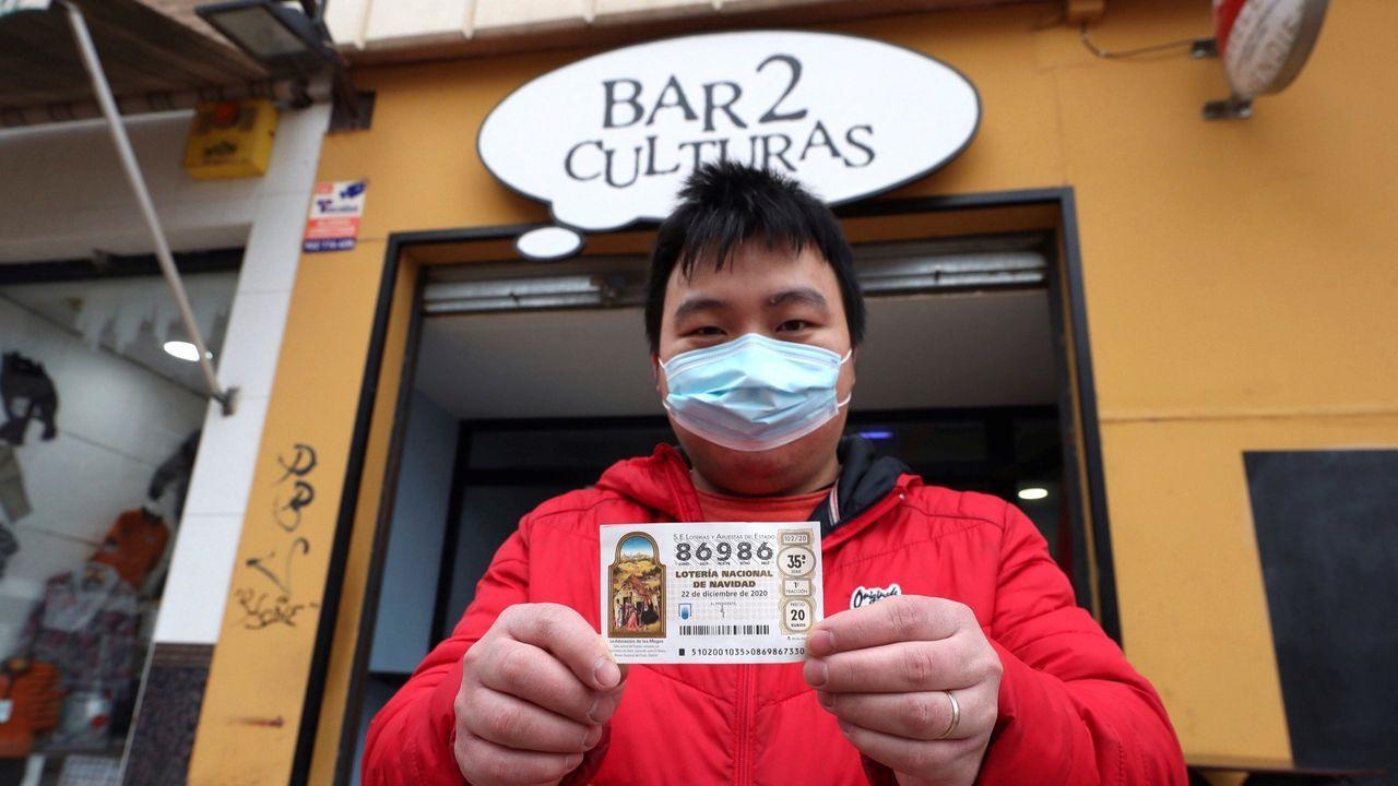 Juan, propietario del bar Dos Culturas de Zaragoza, muestra uno de los décimos agraciados con el quinto premio 86986
