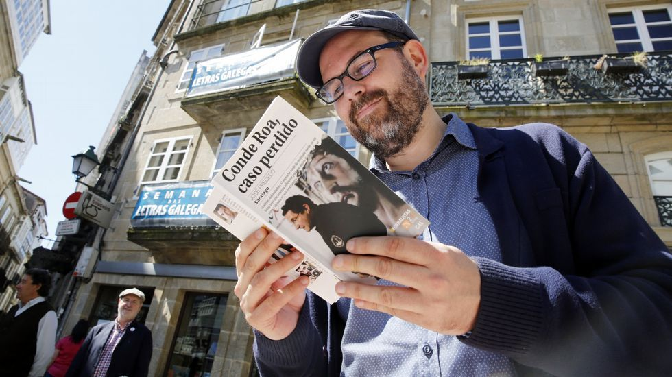 Martiño Noriega, de Compostela Aberta, ojea un libro de Conde Roa durante un Bookcrossing en praza Cervantes