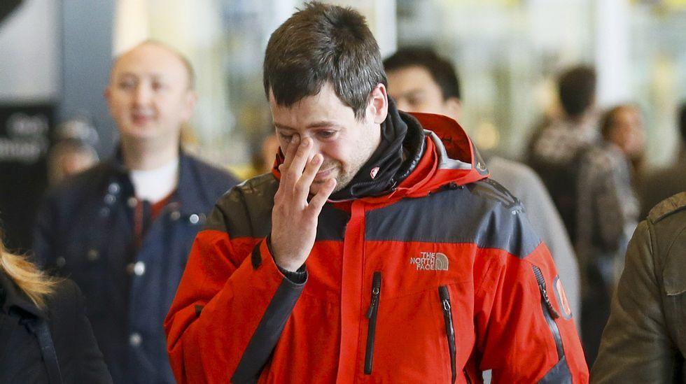 Un hombre transporta flores en las inmediaciones del gimnasio en el que se acogerá a los familiares de las víctimas