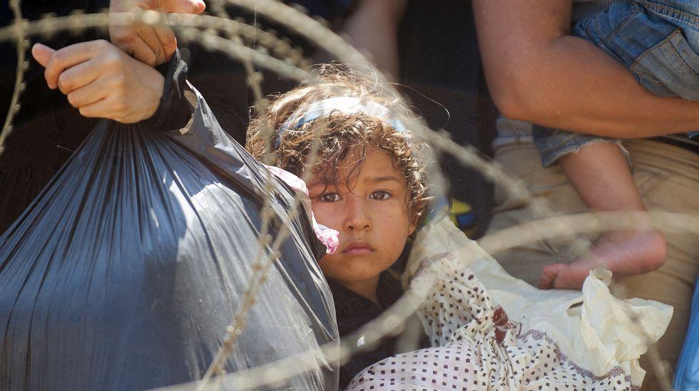 Inmigrantes esperan por la policía de Macedonia para que les permita cruzar hacia el país, en la frontera entre Grecia y Macedonia, con el fin de coger un tren de cara a Serbia