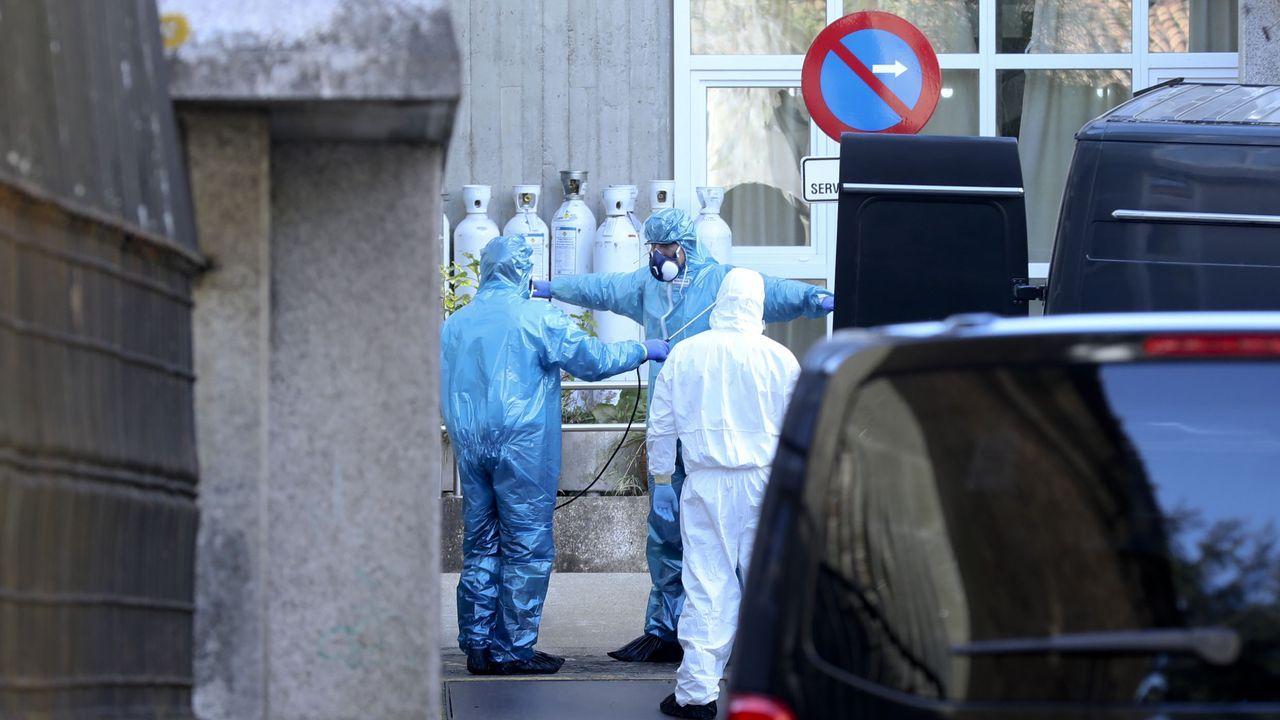 Trabajadores de servicios funerarios se desinfectan tras un traslado en una residencia de Santiago