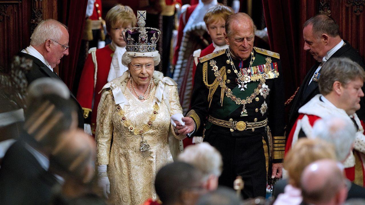 Isabel II de la la mano de su esposo, el príncipe Felipe, duque de Edimburgo, en la Cámara de los Lores durante la apertura del Parlamento en Westminster, el 25 de mayo del 2010