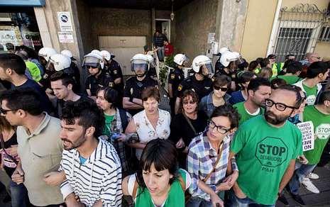 Colectivos antidesahucios formando una cadena humana frente a una casa para evitar el desalojo.