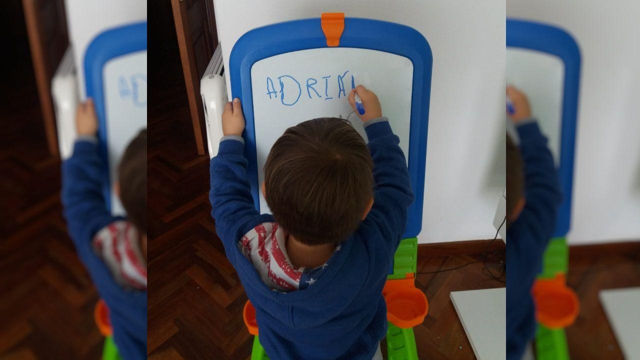 Adrián, que empezó este año el colegio, repasa letras y números en su pizarra