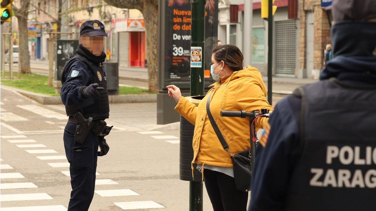 Un policía habla con una mujer protegida con mascarilla durante el estado de alarma, en Zaragoza