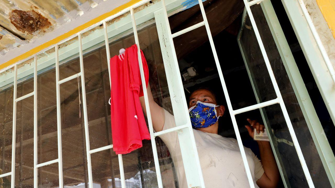 Una niña quita una trapo rojo de su ventana, símbolo con el que se identifican las familias que necesitan comida durante la cuarentena en el municipio de Soacha (Colombia)