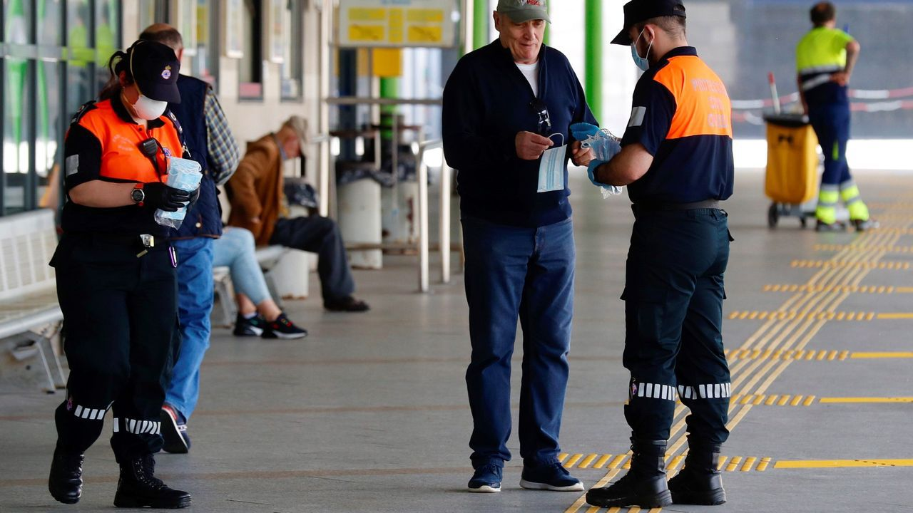 Miembros de protección civil reparten mascarillas este lunes en la estación de autobuses de Oviedo