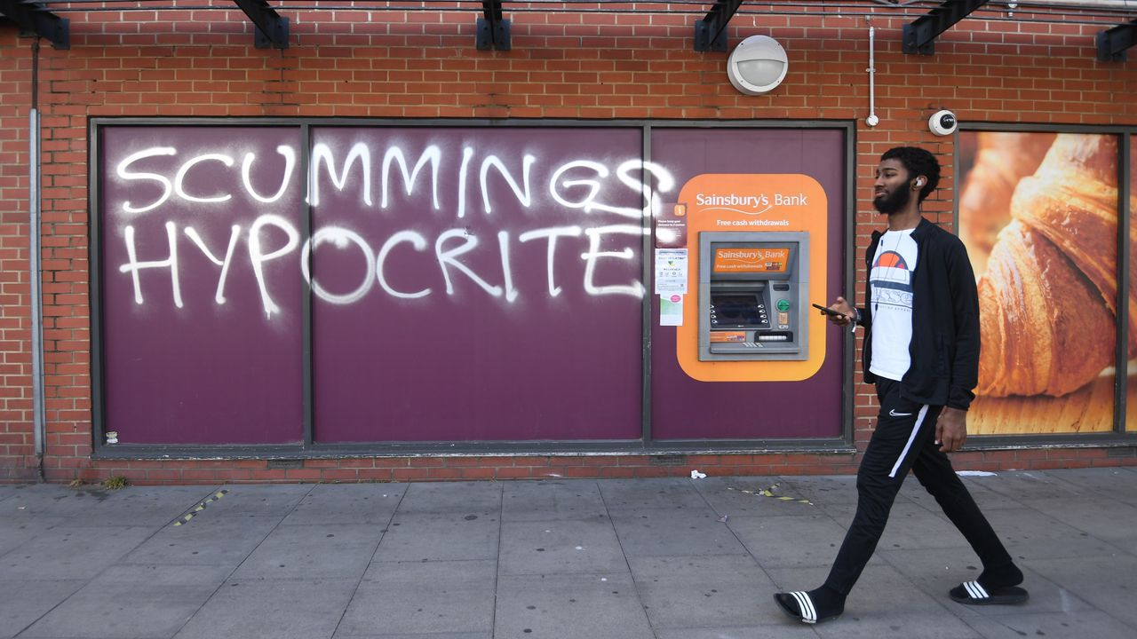Un hombre pasa por delante de un grafiti  contra Dominic Cummings, en Londres