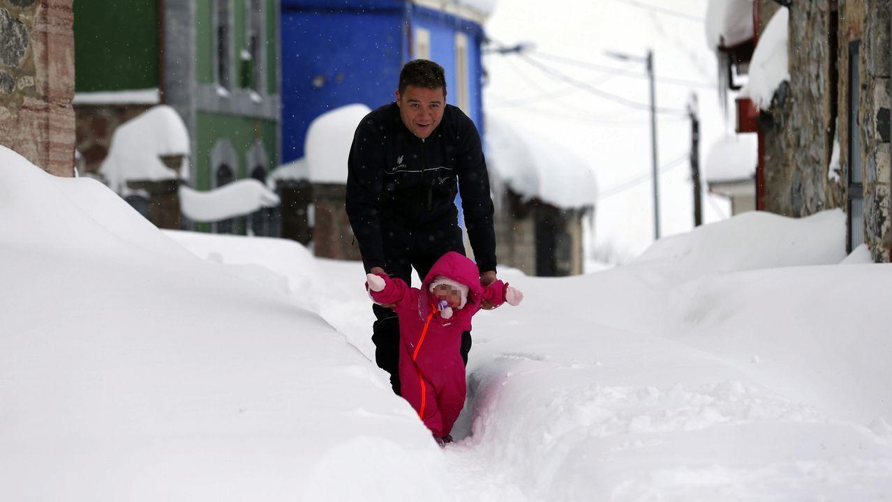 Carretera abierta alrededor de la nieve en Somiedo.Una niña da sus primeros pasos con ayuda de su padre,  sobre la nieve acumulada en las calles del pueblo asturiano de Pajares.