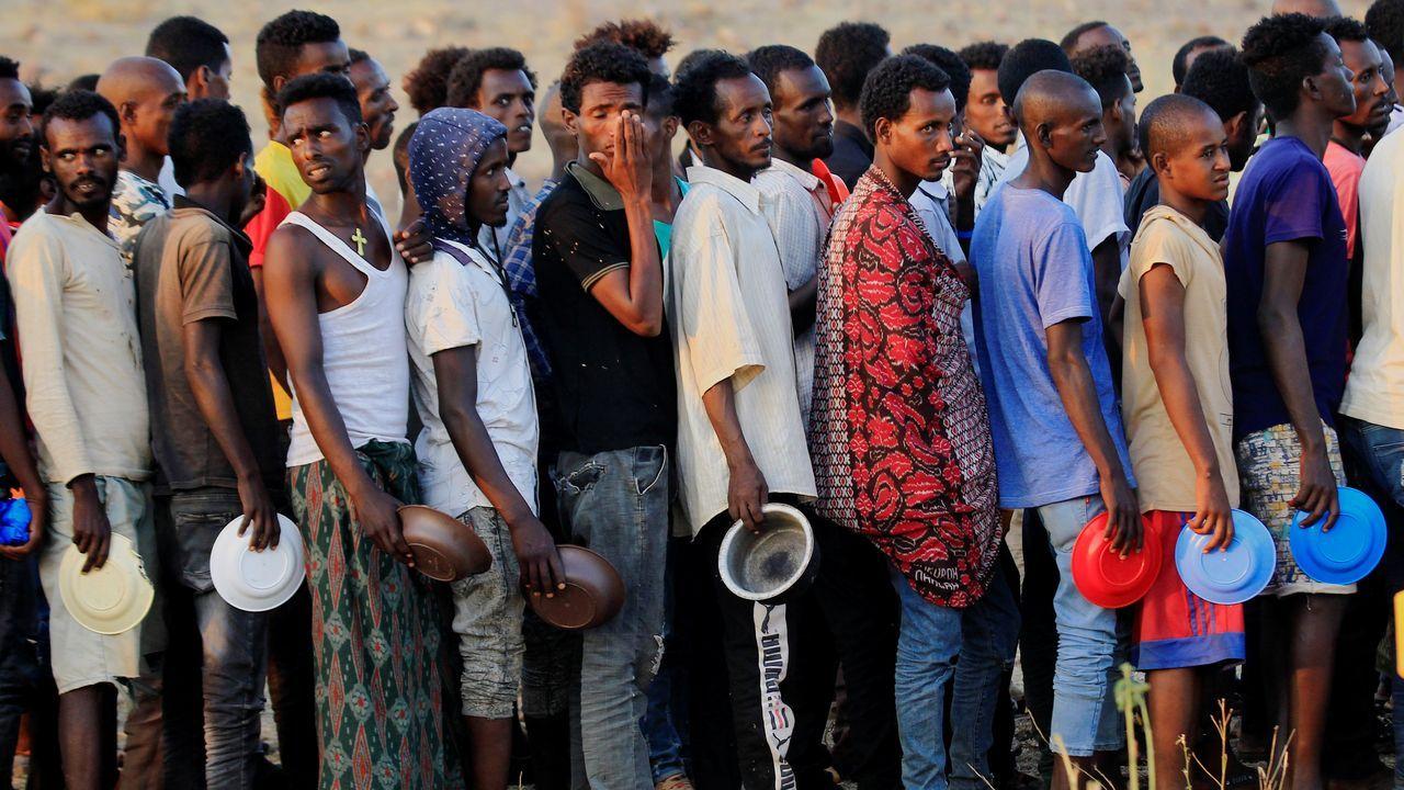 Refugiados etíopes huidos de Tigray hacen cola para conseguir comida en un campamento en la frontera con Sudan