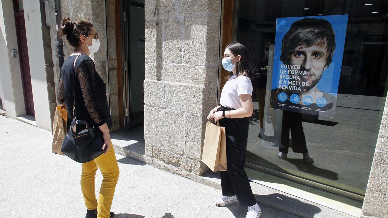 Dos mujeres con mascarilla, este miércoles frente a una tienda de telefonía recién reabierta en Chantada