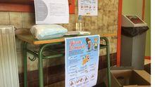 Una mesa con guantes, mascarillas y carteles, en la entrada del IES Monte Naranco