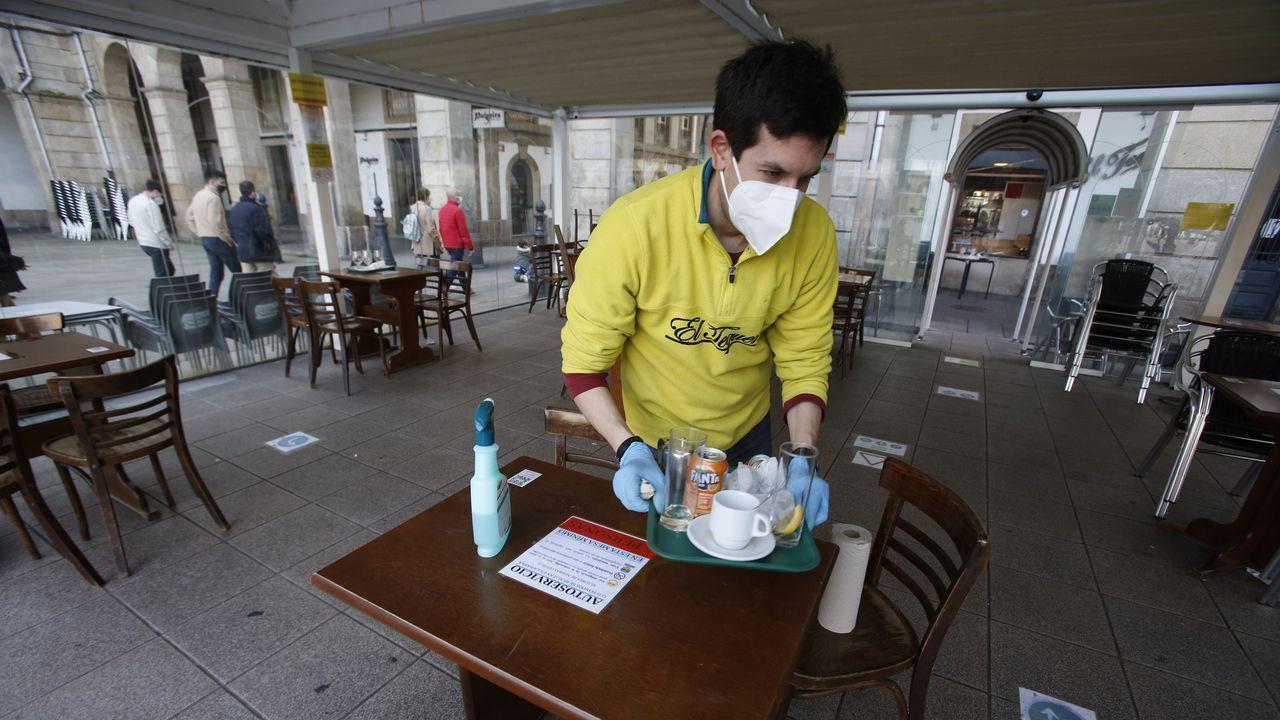 Un camarero recogiendo, al cierre de la hostelería
