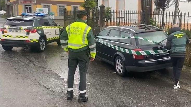 Dos agentes de la Guardia Civil, requisando el coche al paso de la A-6 por Rábade