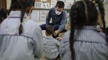 Un profesor pone una mascarilla a un niño de Infantil en el CEIP Raquel Camacho de A Coruña