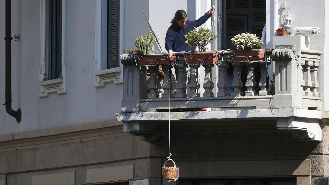 Una mujer tira por la cuerda con la que sostiene un cesto que utiliza para que los viandantes le depositen comida, en Milán