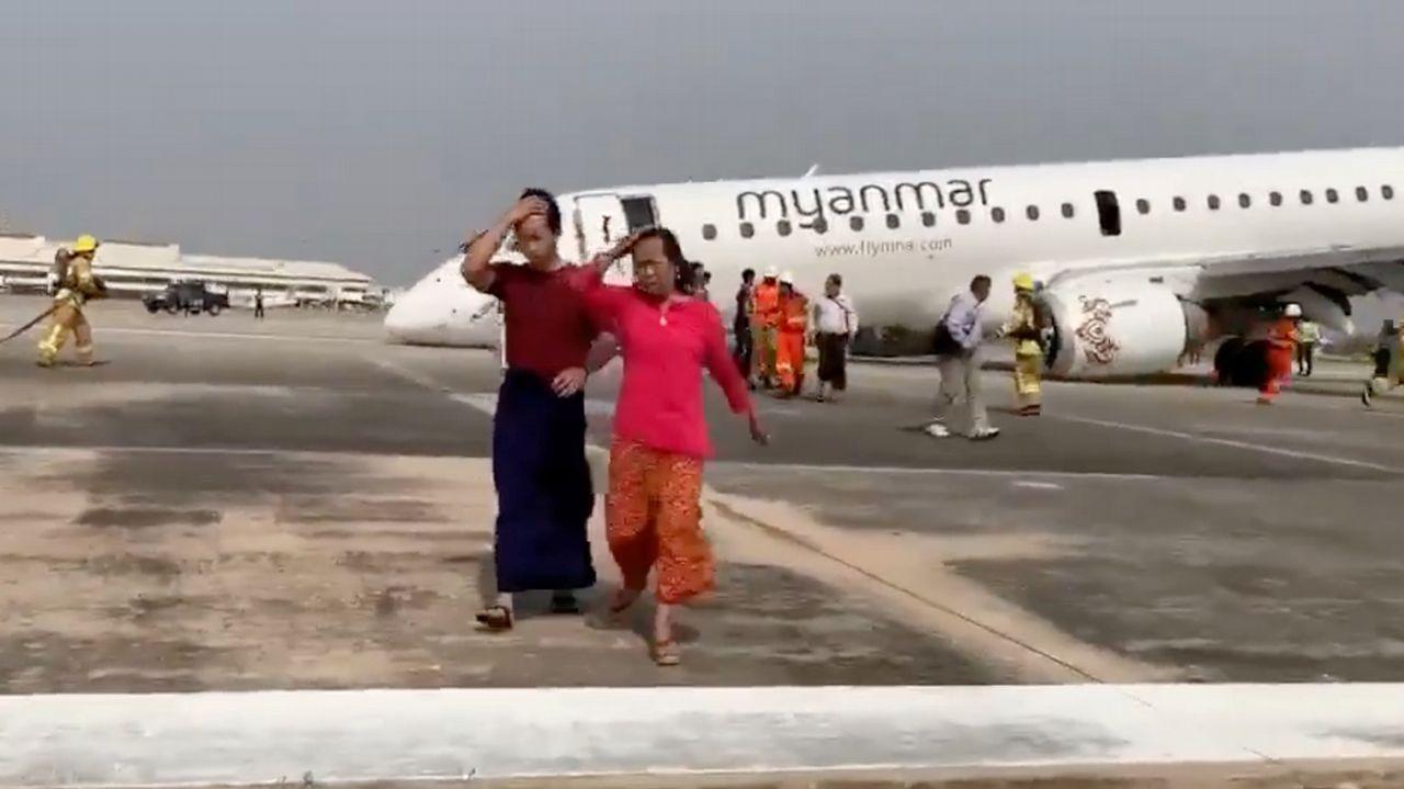 Dos mujeres abandonan el avión sinistrado mientras operan los servicios de emergencias.