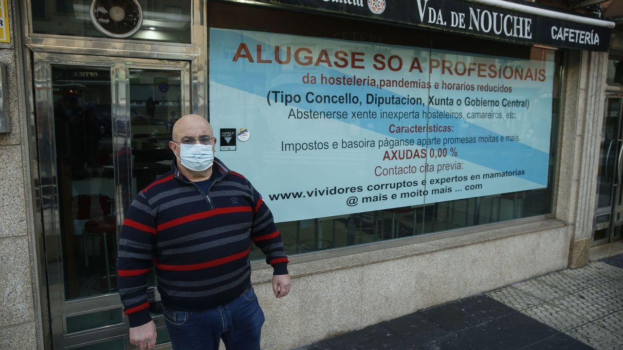 José Regueiro, frente a uno de los carteles que ha colocado en la cristalera de la cafetería Viuda de Nouche de Sigüeiro