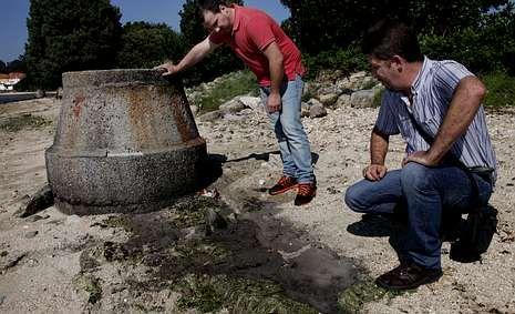 Izado de la bandera azul.Campaña y Maneiro muestran los restos de un vertido.