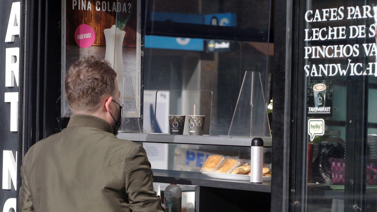 Un hombre compra cafés para llevar en un establecimiento de Gijón, hoy miércoles. Bares, tiendas de ropa, agencias de viaje o inmobiliarias son algunos de los múltiples negocios considerados no esenciales obligados a echar el cierre en Asturias desde este miércoles y durante quince días para tratar de frenar la alta incidencia de la segunda ola de la pandemia de la COVID-19