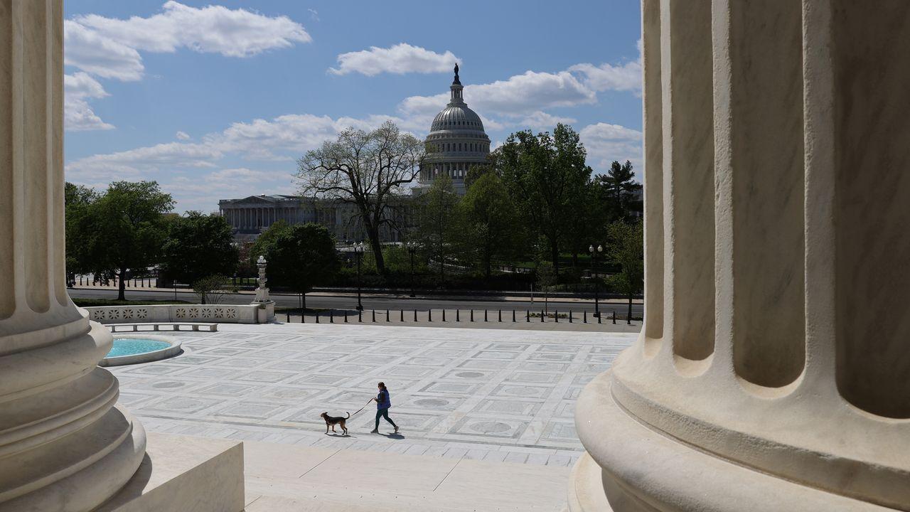 Una mujer pasea a su perro en la explanada del Tribunal Supremo con el Capitolio al fondo