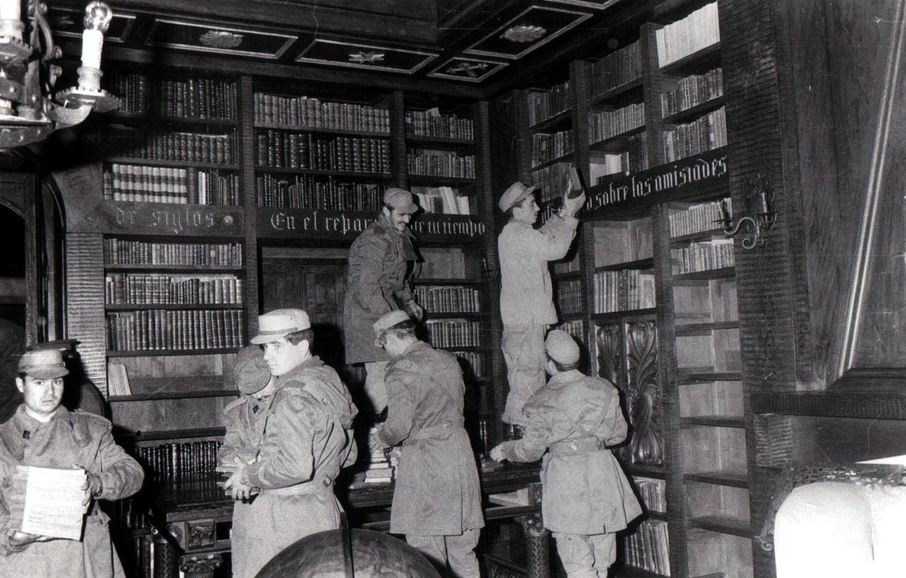 Un grupo de soldados retiran volúmenes de una de las dos bibliotecas de las torres ante el avance de las llamas en la madrugada del 19 de febrero de 1978