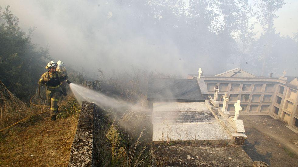 Bomberos forestales apagan el fuego junto a las tumbas del cementerio parroquial de A Vide